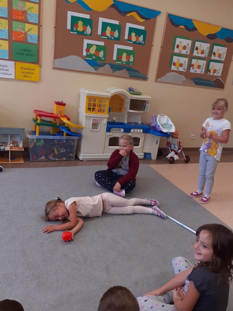 """Dziewczynki z oddziału przedszkolnego prezentują scenkę z bajki """"Królewna Śnieżka"""". Na zdjęciu finał bajki"""