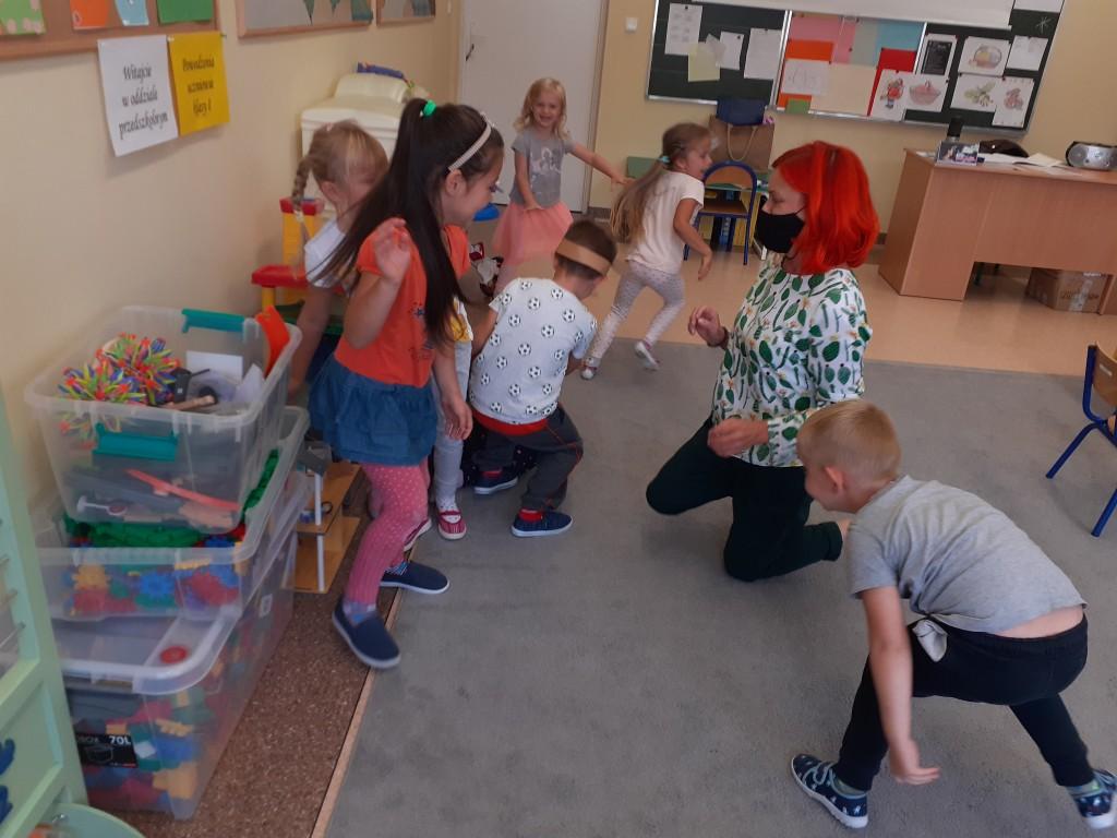 """Wychowankowie z oddziału przedszkolnego wraz z wychowawcą prezentują widowni bajkę """"Wilk i siedem koźlątek"""""""