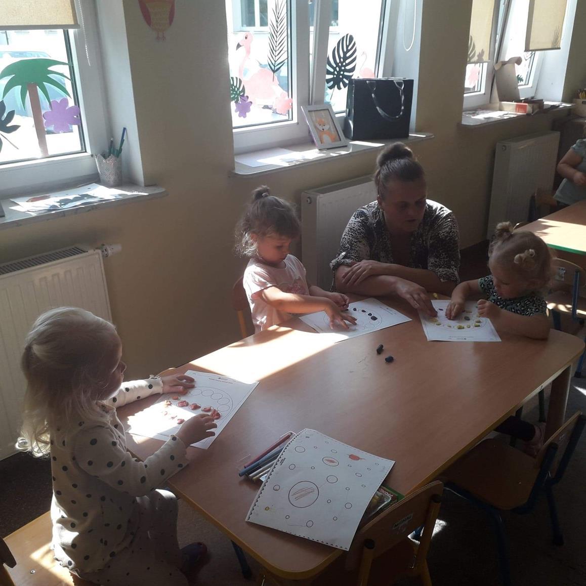 """Zdjęcie przedstawia wychowanków przedszkola z nauczycielem podczas zabaw plastycznych """"Moje kropki"""""""