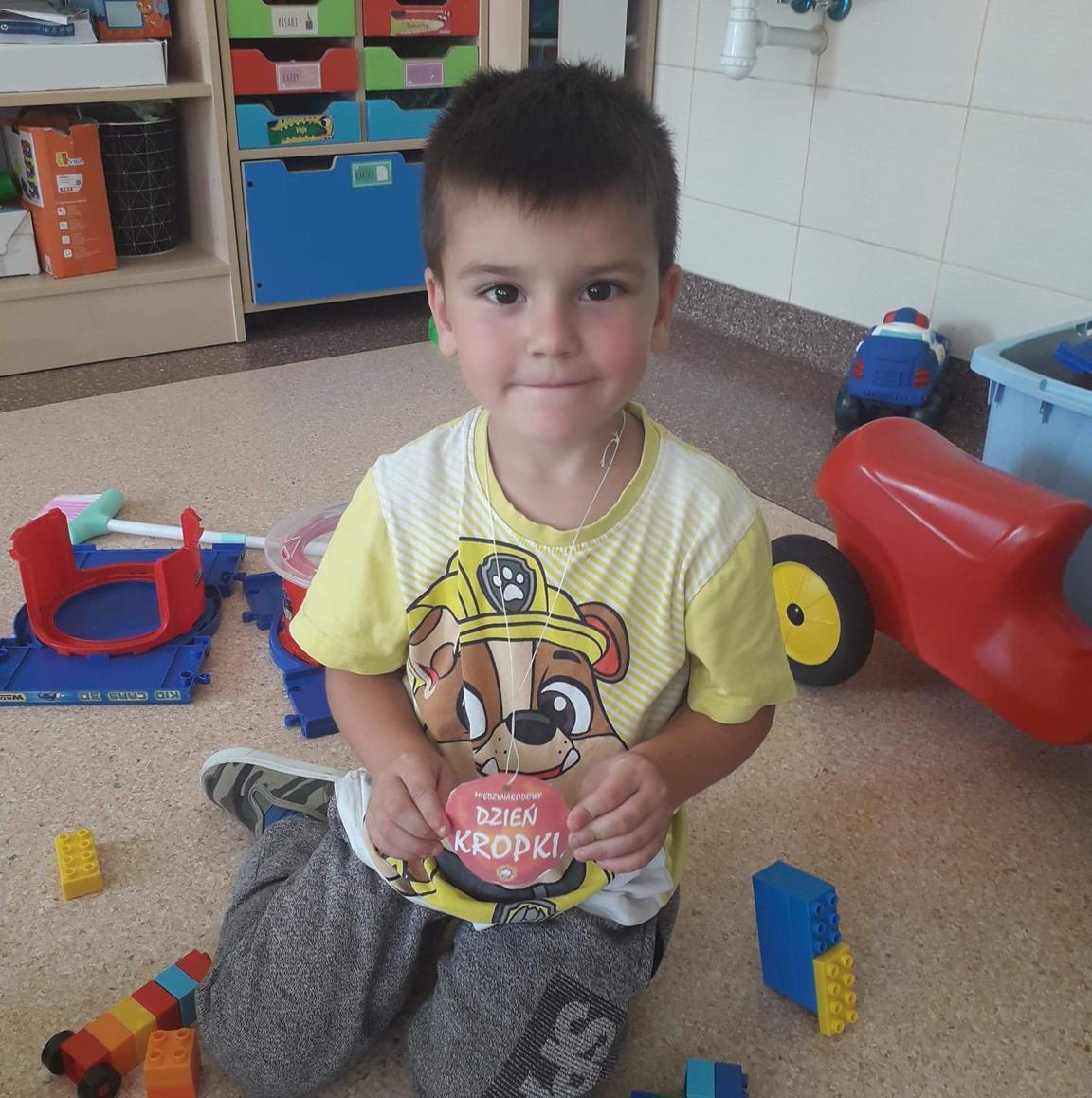 Zdjęcie przedstawia przedszkolaka z emblematem Dzień Kropki