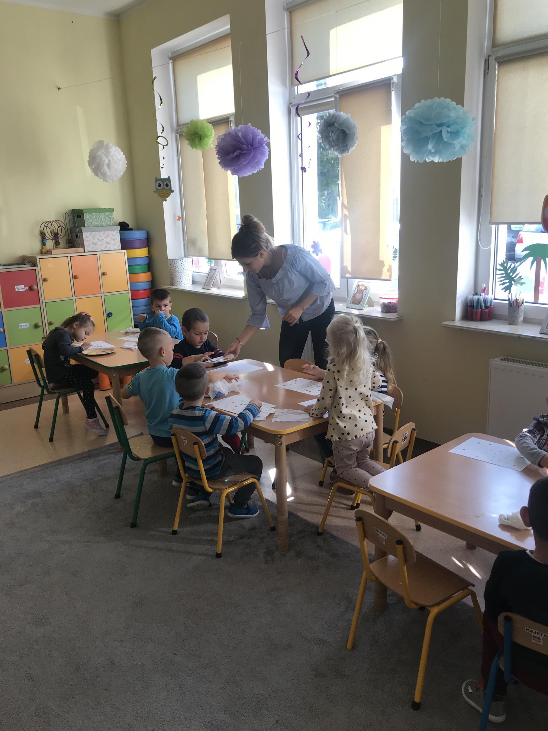 """Zdjęcie przedstawia wychowanków przedszkola z wychowawcą podczas zabaw plastycznych """"Moje kropki"""""""