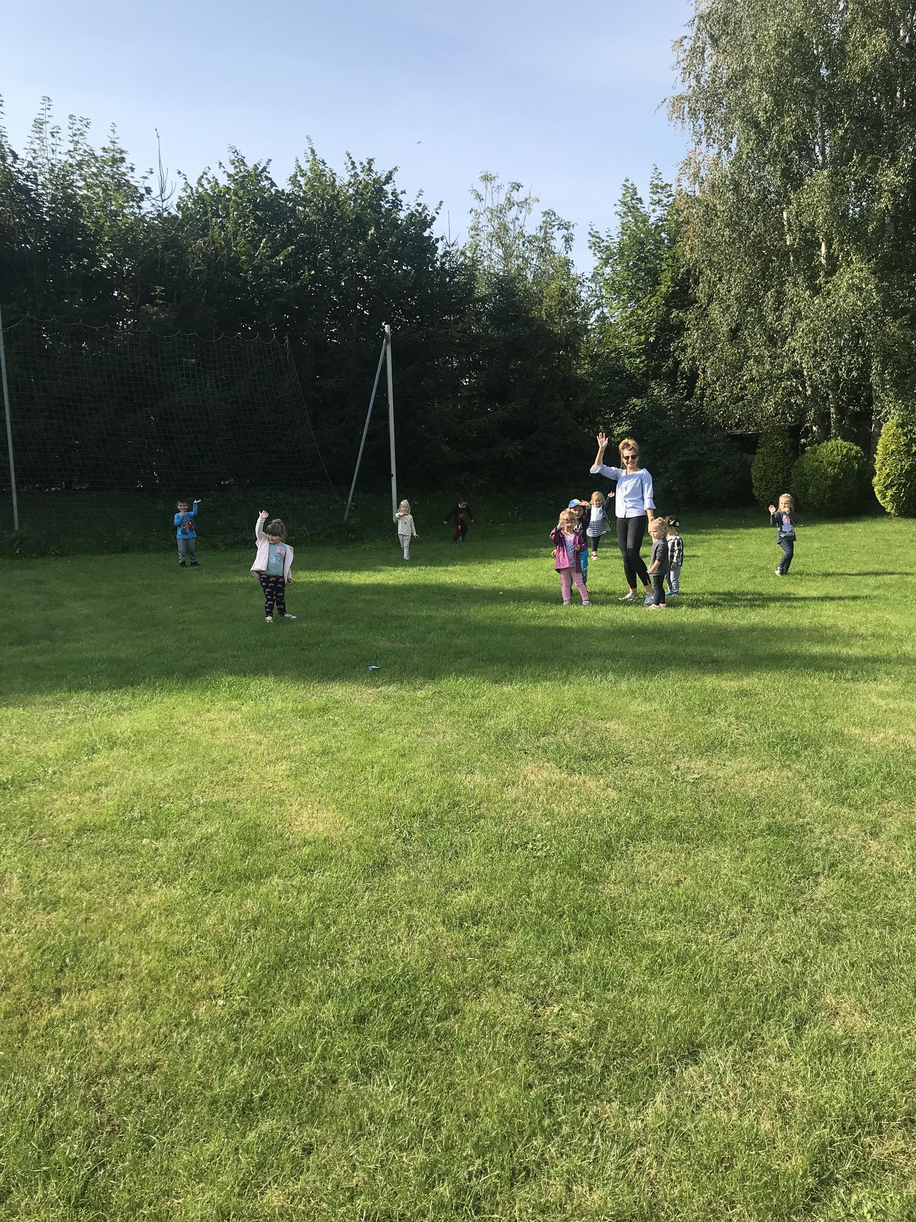 Zdjęcie przedstawia wychowanków przedszkola podczas zabawy w ogrodzie przyszkolnym