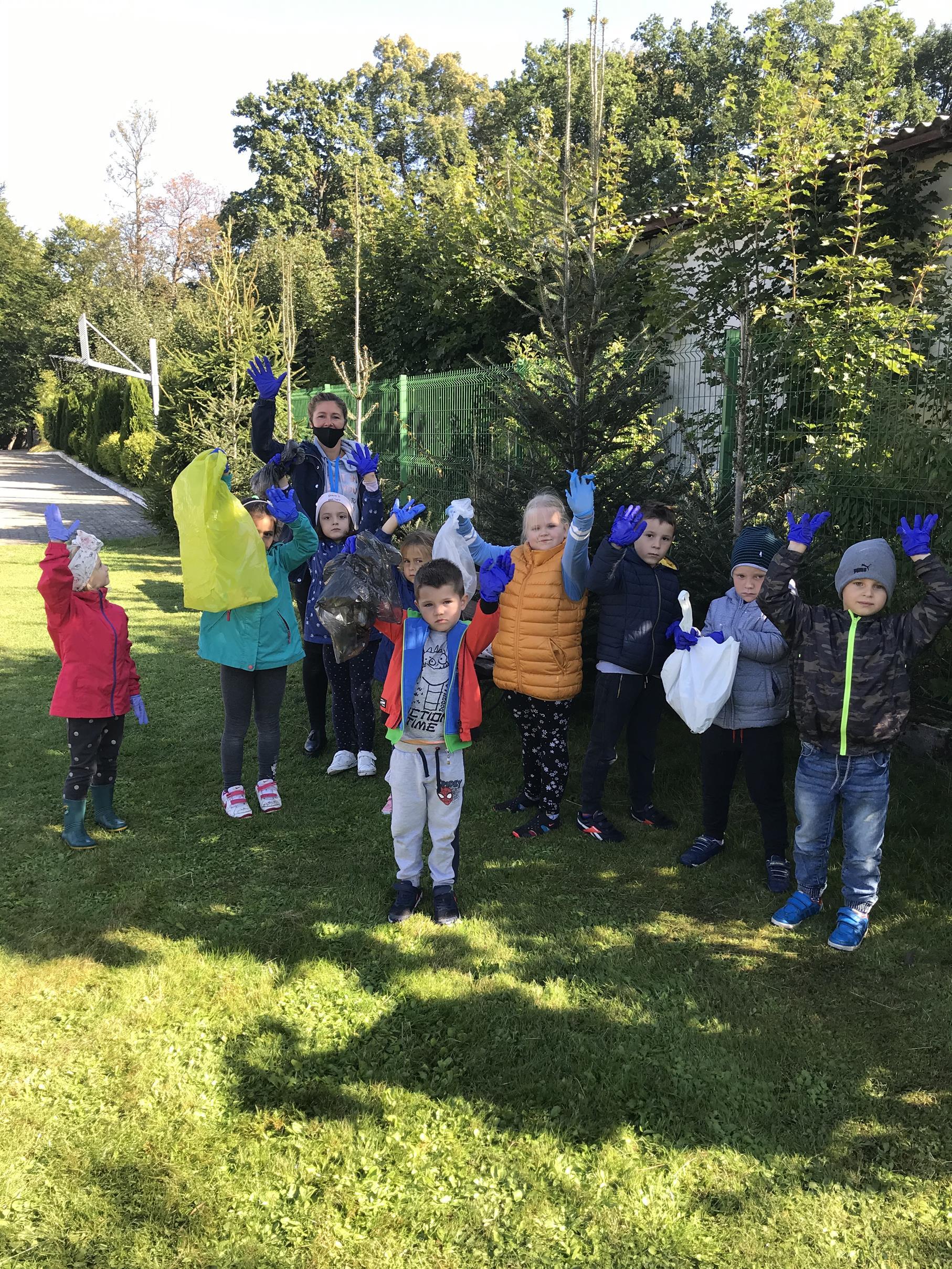 Dzieci z oddziału przedszkolnego z nauczycielem w czasie porządkowania terenu ogrodu przyszkolnego