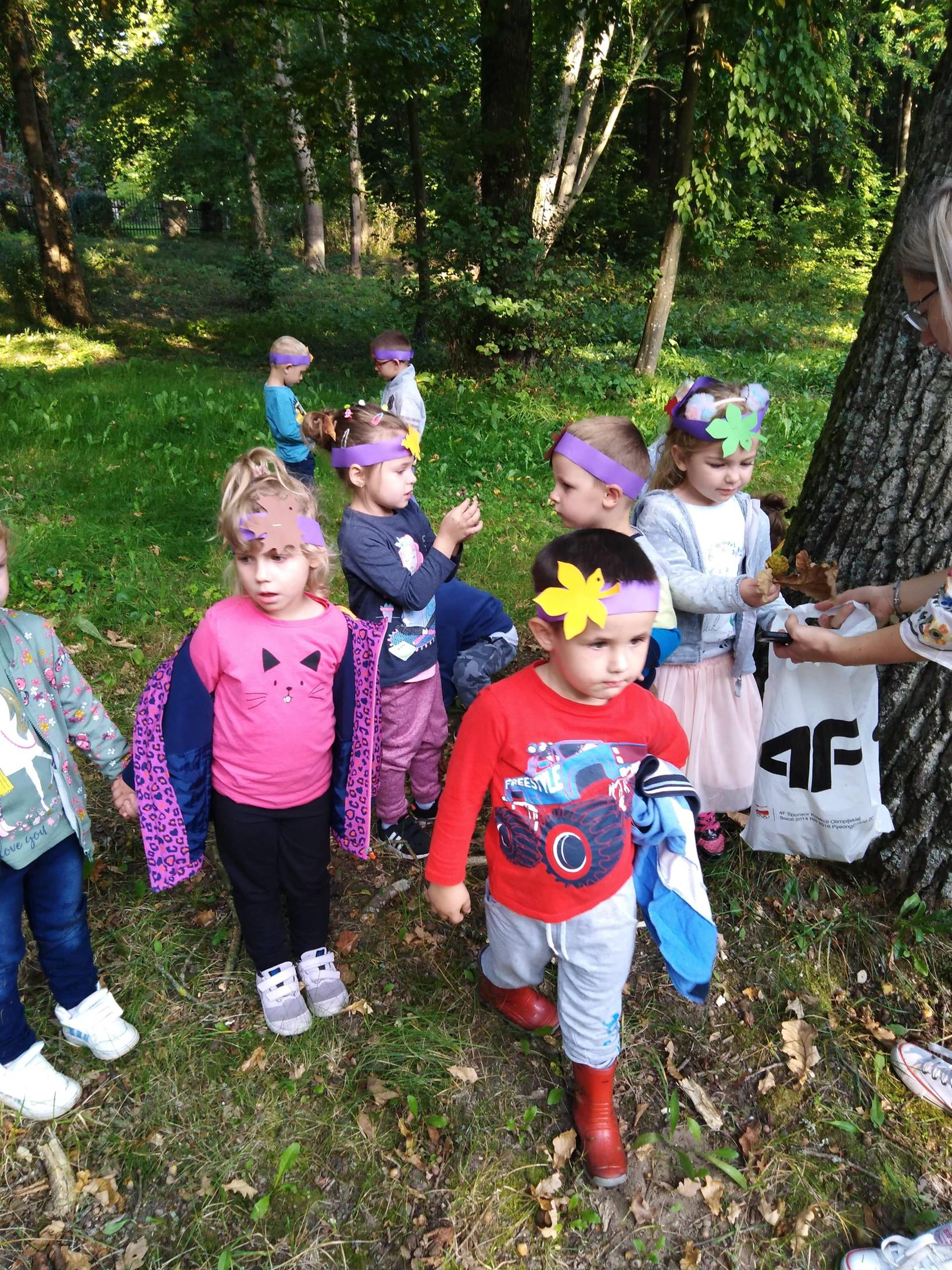 Przedszkolaki podczas zabaw z kolorowymi liśćmi