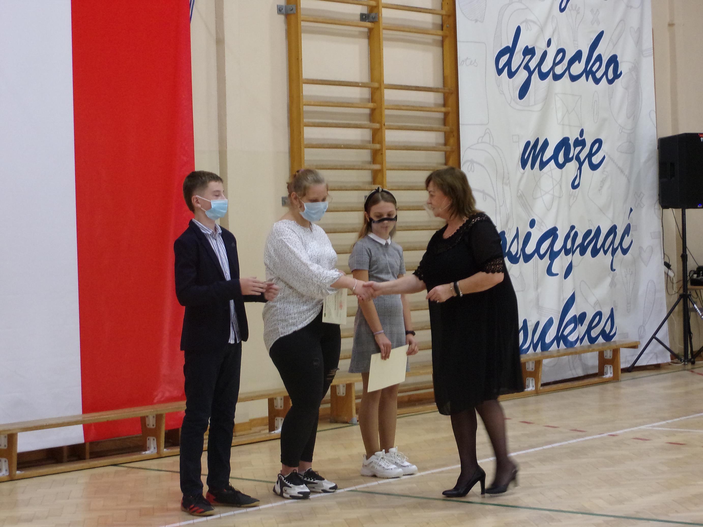 Pani dyrektor Iwona Nowak Gancarz gratuluje uczniom podpisania Aktu Ślubowania
