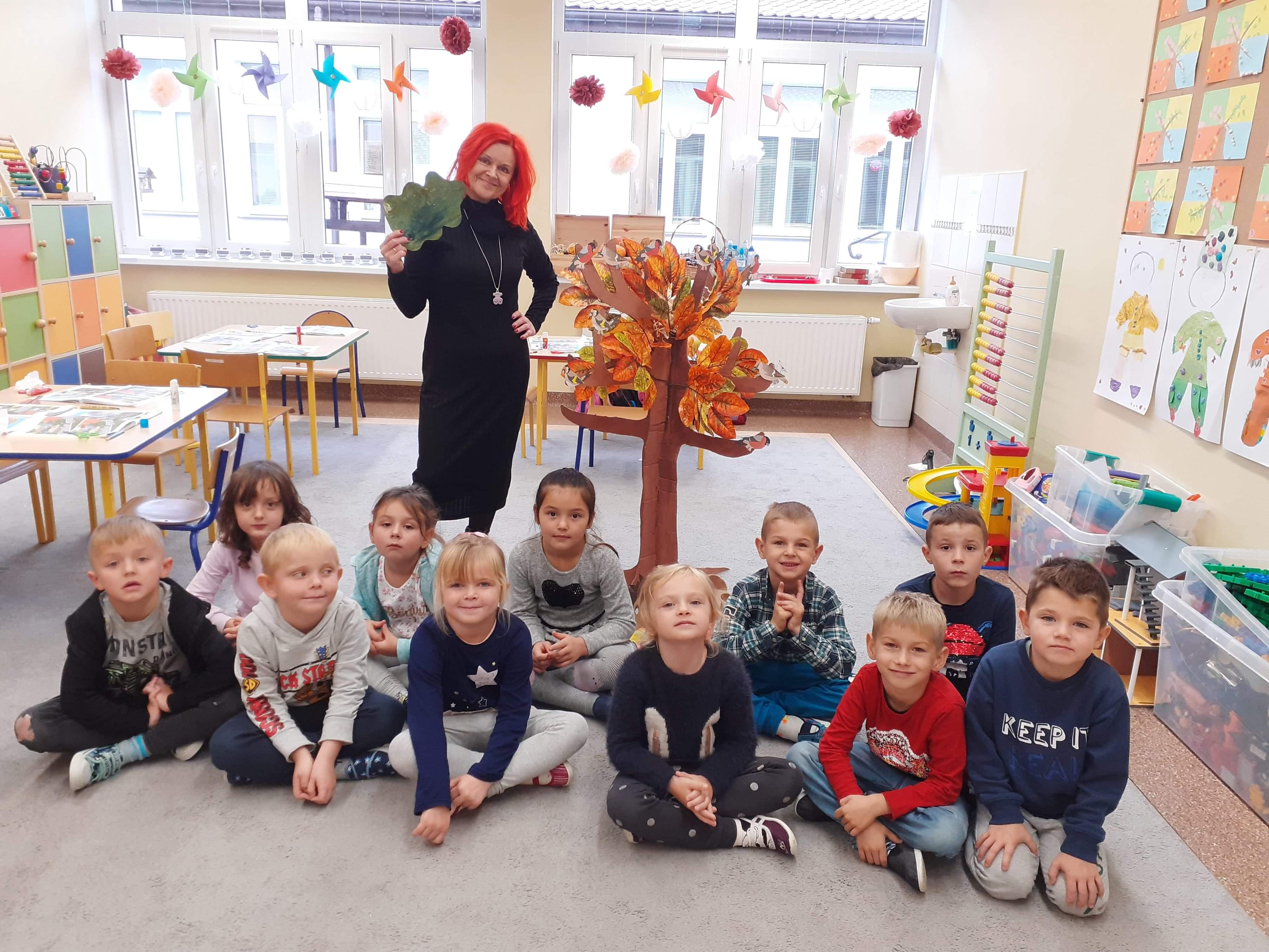 Wychowankowie oddziału przedszkolnego z wychowawcą prezentują wykonaną pracę przestrzenną :Drzewo schronieniem dla zwierząt