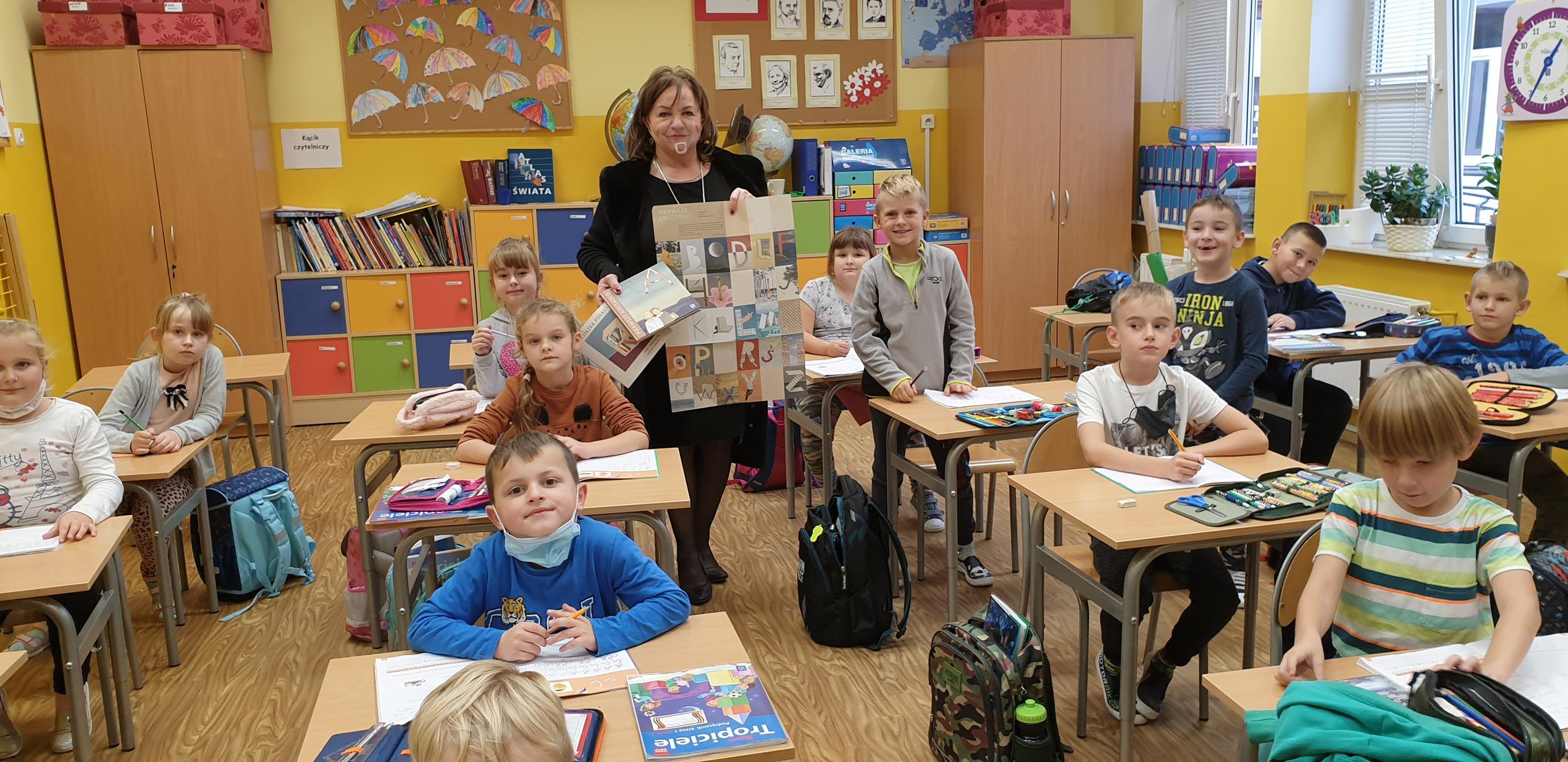 Pani dyrektor Iwona Nowak-Gancarz prezentuje uczniom klasy I Wyprawkę Czytelniczą.