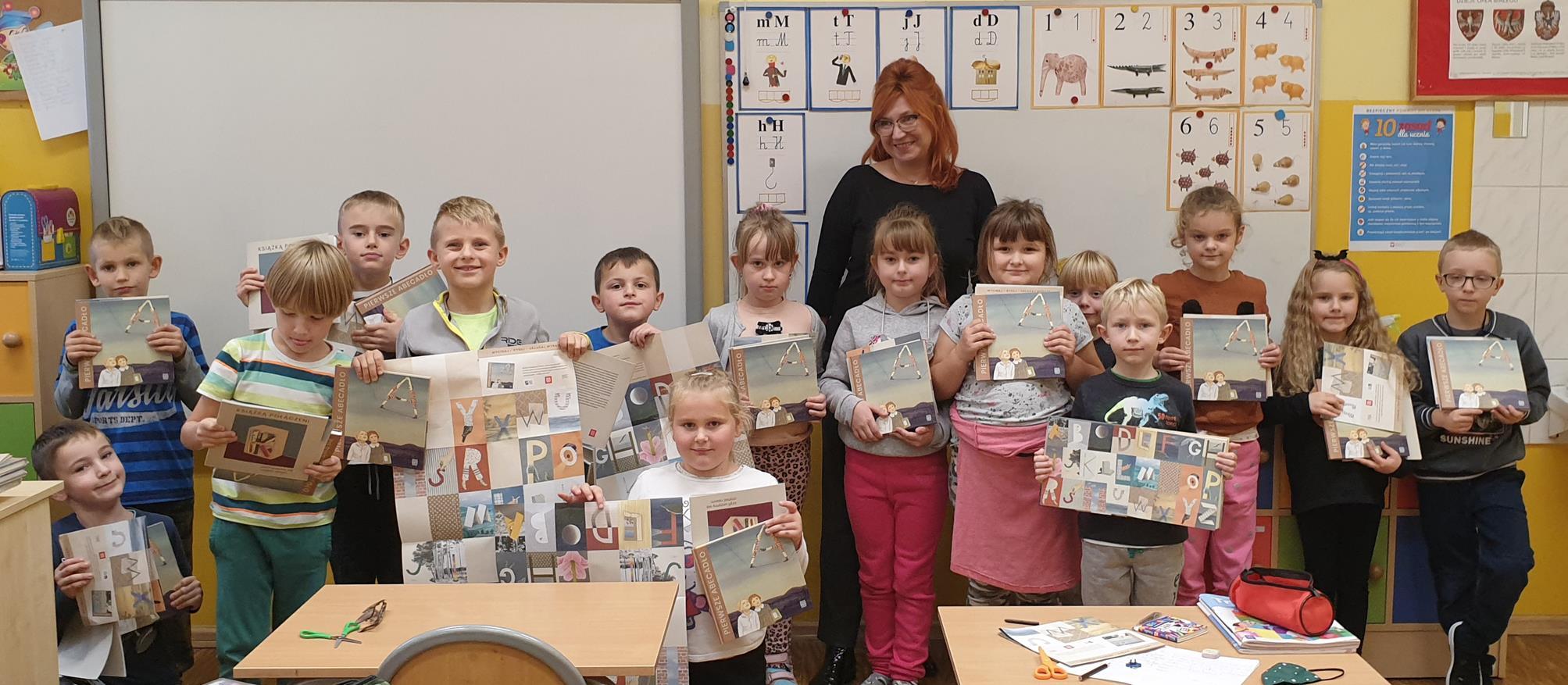 Uczniowie klasy I razem z wychowawcą demonstrują swoje prezenty w postaci książek i kreatywnego alfabetu.