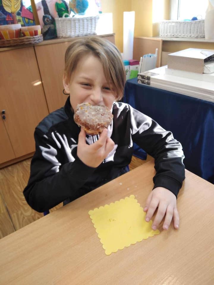 Uczeń klasy trzeciej podczas degustacji pączków