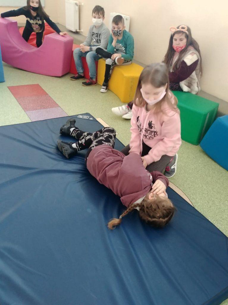 Uczniowie klasy drugiej w czasie ćwiczenia układania pozycji bocznej bezpiecznej