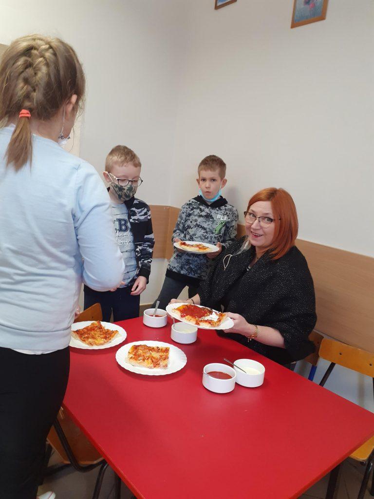 Wychowawca klasy I wspólnie z uczniami kroi pizzę