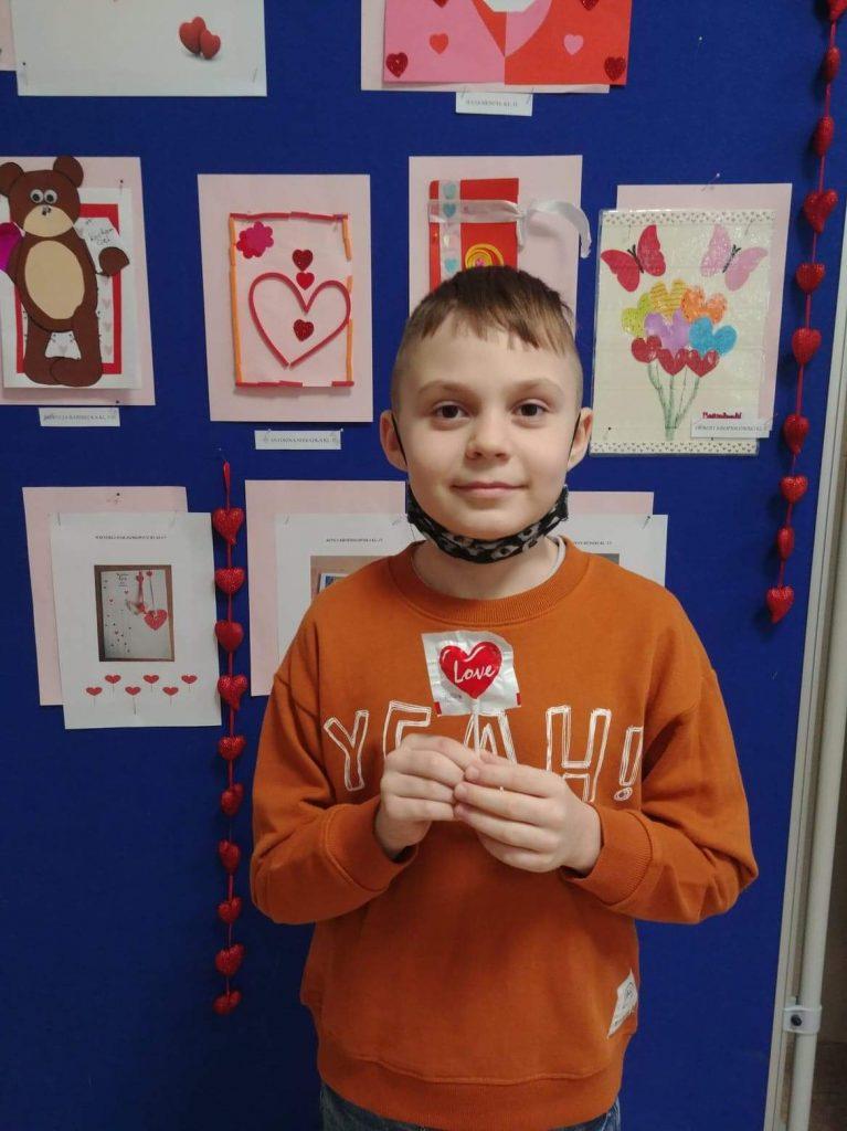 Uczeń klasy drugiej prezentuje swoją kartkę walentynkową