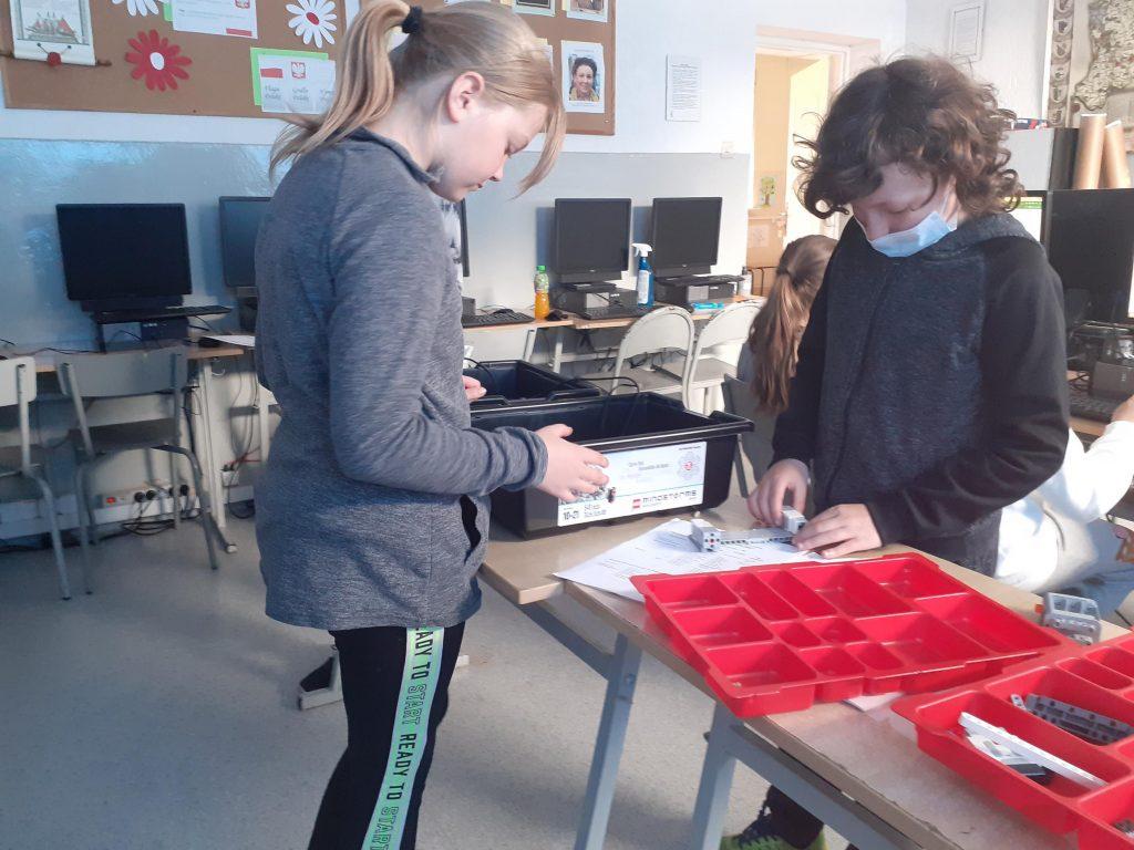 Uczniowie klasy piątej w czasie zabaw z robotami