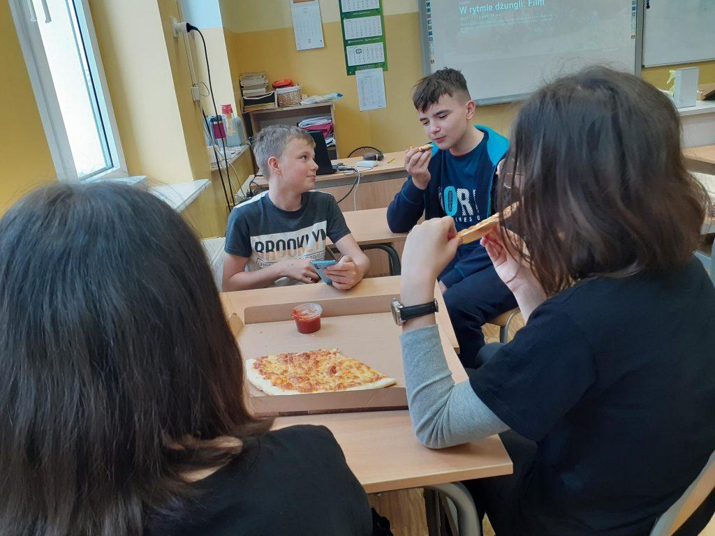 Uczniowie klasy szóstej w trakcie zajadania pizzy