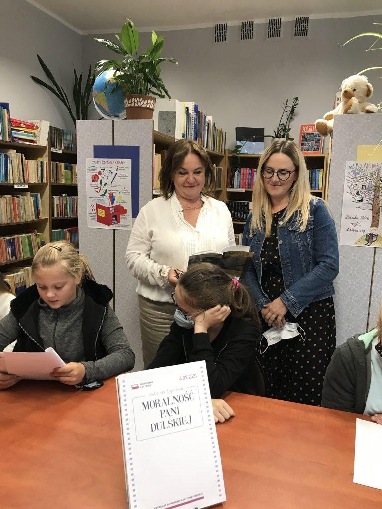 Uczniowie klasy szóstej z panią dyrektor szkoły w trakcie Narodowego Czytania
